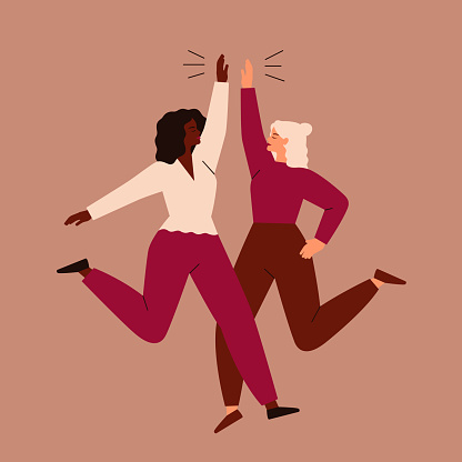 Two women jump and high-five each other.