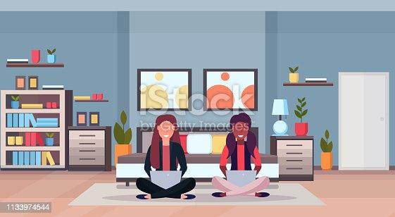 two women sitting lotus pose on floor using laptop mix race girls smiling modern home living room interior design female cartoon characters full length flat horizontal vector illustration