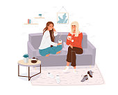 Two young women spending time together. Girls cosy sitting on the couch, talking and holding cup tea, coffee. Home or cafe style modern vector illustration.