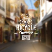 Type design with bicycle silhouette against a street defocused background