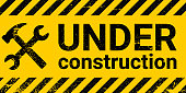 istock under construction site banner sign vector black and yellow diagonal stripes under construction, hammer and wrench repair sign with grunge texture 1192837450