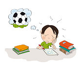 Overworked little schoolboy sitting behind the desk with piles of books next to him, writing homeowork and feeling tired. He is dreaming about playing football outside in the park or in the garden.