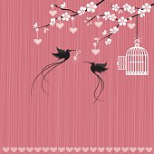 A bird with a heart shaped key in it's beak has freed another bird from it's cage. Hearts hang from ribbons tied to the branches of a cherry blossom tree.