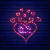 Valentines day neon sign with bright lettering text and heart shapes. Valentine greeting emblem design in neon style. Vector illustration.