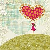 Little girl holding a big heart.