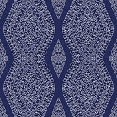 Vector abstract wavy seamless pattern from light beige hand drawn outline ornate rhombus, Eskimo ornaments, wavy stripes on a navy blue  backgrpund. Textile fantasy print. Wrapping paper. Batik painting