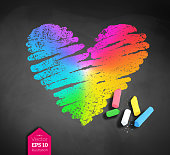 Vector sketch of rainbow colored heart and pieces of chalk with shadow on blackboard background.