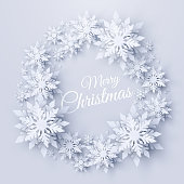 Vector Merry Christmas and Happy New Year background with christmas wreath made of realistic looking paper cut snowflakes. Seasonal winter holidays greeting card
