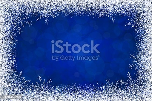 Christmas holidays white frame with snow and snowflakes on dark blue background. The eps file is organised into layers for the background, the bokeh, the frame and the snowflakes.
