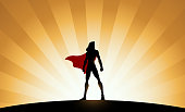 A silhouette style vector illustration of a female superhero standing with sunburst effect in the background. Easy to edit. Wide space available for your copy.