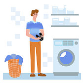 Vector flat illustration with man who is washing things and shoes, sneakers. Separately depicted washing machine, basket with dirty laundry. Concept of hygiene, self service, cleaning.