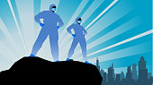 A silhouette style vector illustration of a couple of healthcare workers in personal protective equipment depicted as superheroes. Sunburst and city skyline visible in the background. Wide space available for your copy.