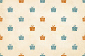 Vector Illustration of a semi seamless Xmas grunge background (design only, not grunge)  Vintage colours, beige, pale green blue and dull orange brown wrapped up gift boxes, over a pale yellowish grunge backdrop. No text, no people, Can be used as a wallpaper, Xmas or New Year background, birthday celebration background, gift wrapping sheet . The gift boxes are wrapped up by a ribbon and tied into a two looped bow with forked ends. The gift boxes have a dotted curved pattern detail.  The boxes are uniformly / evenly placed over the yellowish beige colored backdrop.