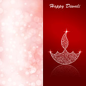 Vector illustration of an illuminated Diya. The illustration is divided into two equal vertical bands. The left band is a soft baby pink glittery background. The right half is a reddish maroon vibrant Deepawali background with twinkle on the Deepak and flame. The Diya and flame are made up of small dots glitter. There is reflection of the Diya at its base. Traditional Indian festival, Diwali is celebrated by lighting Diyas or Deepaks. Happy Diwali is written at the top right of the illustration.