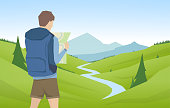 Young man traveler and hiker with map on summer mountains flat landscape background
