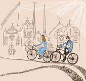 Vector image of young couple riding bicycles in fairy tale town.