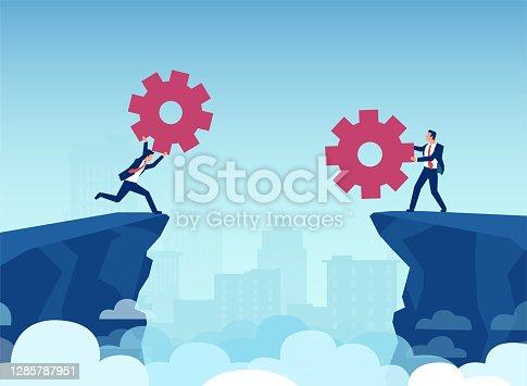 istock Vector of businessmen using gears to bridge the cliff gap between them 1285787951