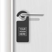 Vector realistic paper black blank door hanger on white realistic wooden door with metal silver handle. Door hanger mockup. Design template. Full length door is in a clipping mask.