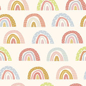 Vector seamless pattern of cute cartoon rainbows on an isolated white background. Hand drawn rainbow. Illustration of children on a greeting card, a print on fabric, clothes and wrapping paper. Flat