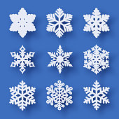 Vector set of 9 white Christmas paper cut snowflakes with shadow on blue background. New year and Christmas design elements