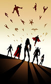 A vector silhouette style illustration of a flying army of superheroes. Wide space available for your copy.