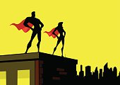 A flat color silhouette illustration of a superhero couple on top of a building with a city skyline in the background. Wide copy space available for your text.