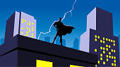 A silhouette style vector illustration of a superhero standing on a building rooftop with lightning strike and city skyline in the background.