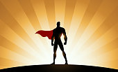 A silhouette style illustration of a superhero standing with sunburst effect in the background. Easy to edit. Wide space available for your copy.