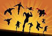 A silhouette style illustration of a team of superheroes running, flying , and charging forward approaching the screen.