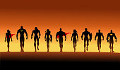 A silhouette style vector illustration of a team of superheroes walking in group. Wide space available for your copy.