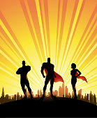 A silhouette style illustration of a team of superheroes consisted of three people with city skyline and sunburst in the background. Wide space available for your copy.