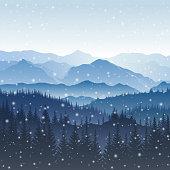 Vector winter landscape with blue silhouettes of mountains and trees in the forest and falling snowflakes