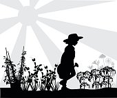 Silhouette illustration of little girl walking through her vegetable garden and carrying water.  She is wearing a gardener's hat.