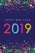 Vibrant and modern greeting card for New Year 2019 with confetti and 2019 number placed on dark purple background.
