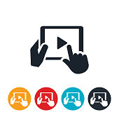 An icon of hands holding a tablet PC while pushing the play button on the screen to play a video.