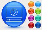 Video Player Interface Icon. This 100% royalty free vector illustration is featuring a blue round button with a drop shadow and the main icon is depicted in white. There are eight more color variations included on the right side of the image.