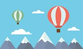 View of two colorful hot air balloons jetting over mountain tops among clouds on blue sky - vector