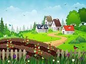 Countryside village landscape with rural houses, vegetable garden and green meadows under blue skies.