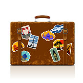 Vintage brown threadbare suitcase with collection of retro grunge vacation & travel labels