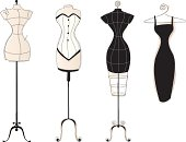 Three vintage-style dress forms and a little black dress on a hanger.