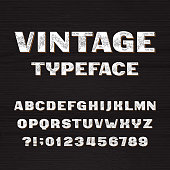 Vintage typeface. Retro alphabet font. Type letters and numbers on a rough wooden background. Vector font for your headers or any typography design.