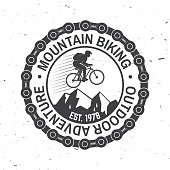 Mountain biking. Vector illustration. Concept for shirt or logo, print, stamp or tee. Vintage typography design with man riding bike, chain and mountain silhouette. Outdoor adventure.