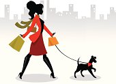 A fashionable woman shopping and walking her dog.