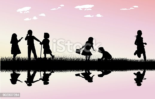Small kids playing by the water in front of a beautiful body of water with pink skies behind them
