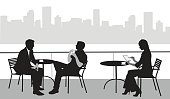 A vector silhouette illustration of a young woman using a tablet while sitting at an outdoor cafe patio with two other business men sitting at another table.  The patio overlooks a body of water with a city scape in the background.