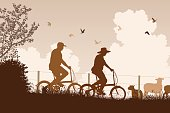 Editable vector silhouette of a couple cycling together in the countryside