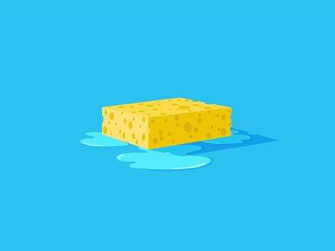 Wet yellow sponge on a floor.