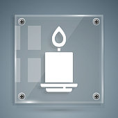 White Burning candle icon isolated on grey background. Cylindrical aromatic candle stick with burning flame. Happy Halloween party. Square glass panels. Vector.