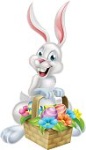 A white cartoon Easter bunny rabbit mascot character holding an Easter basket full of chocolate Easter eggs on an Easter egg hunt