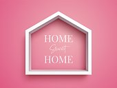 """White frame in shape of house on pink background with inscription """"Home Sweet Home"""". Real estate symbol"""